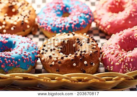 Colorful donuts in different colors in a whicker basket