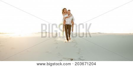 Groom carries bride on his back across sand dune in desert. They going on background of white sand.