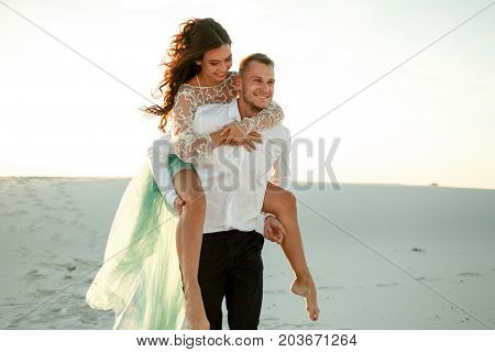 Groom carries bride on his back across sand in desert. They going on background of white sand and laugh cheerfully. Close up.