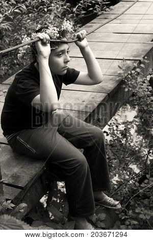 Sad boy sitting on wooden bridge and misses.
