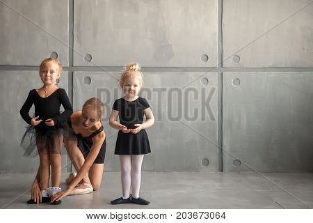 Young beautiful blonde woman ballet dancer in black dress bulging pantyhose and pointe shoes tying pointes to small fair-haired girls ballerines in black dresses in a dark dance studio