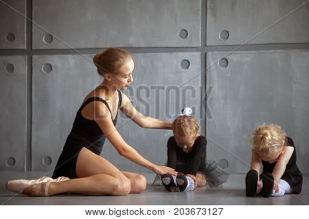 A beautiful adult blonde Russian ballerina in a black tutu and white pantyhose helps to stretch two little girls to ballerinas
