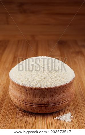 Semolina in wooden bowl on brown bamboo board closeup. Rustic style healthy dietary groats background.
