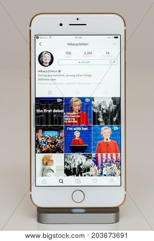 PARIS FRANCE - SEP 26 2016: New Apple iPhone 7 Plus in docking station after unboxing and testing by installing and running the app application software Instagram with hillary Clinton president candidate account feed