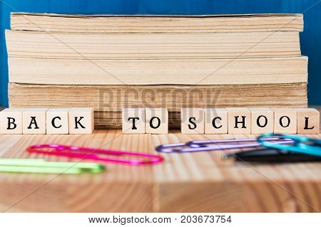 Back to school caption made out of letter tiles. Books on a desk with paper clips.