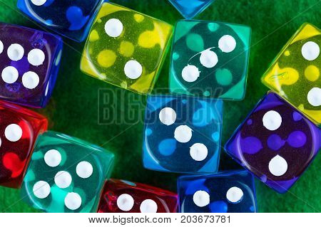 Colorful dice on a green casino background. Flat lay top view.