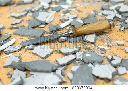 The chisel lies in the middle of pieces of cement and plaster. Dirty, littered workplace.