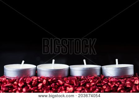 Four candles in a row for Advent season in Christian church. Copy space at the top.