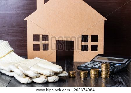 Home heat savings or expenses concept. Warm gloves coin stacks calculator house shape.