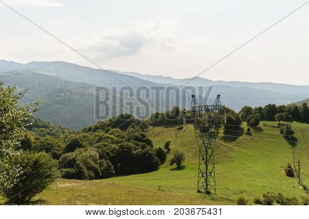 massive electricity pole in nature green vegetation covered mountains in background. high voltage electricity pillar