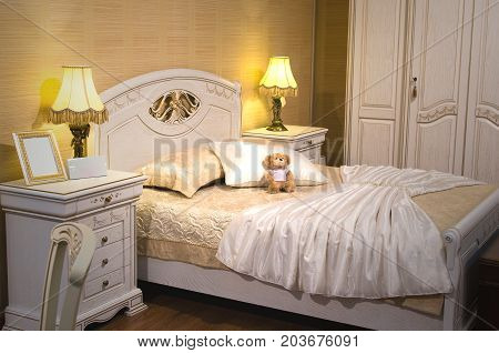 Luxury bedroom interior in vintage style. Empty photo frame on the bedside table. Teddy bear and white dress on the bed.