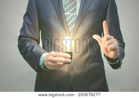 Find solution concept. New idea concept. Business inspiration. Business man with a burning lamp in one hand and showing forefinger thumb up sign another hand.