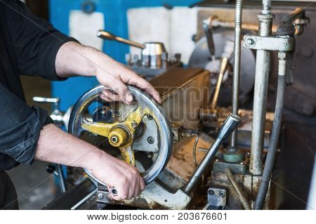 The hands of the turner rotate the wheel of the quill of the lathe. Operation of drilling on a lathe. poster