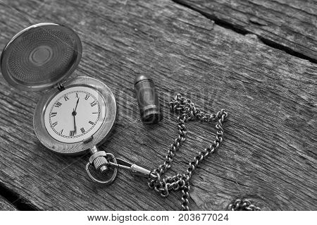 Retro watch with Roman Numerals laid next to the pistol cartridge. In black and white