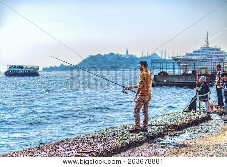ISTANBUL, TURKEY: A young man with a fishing rod is fishing on the Bosphorus embankment on October 7, 2014