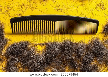 Comb and beard trimmings on a bright yellow background. Concept for male grooming and style concious men for movember