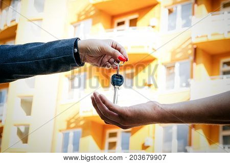 Concept Of Buying, Selling And Renting Housing. A Woman's Hand Passes The Keys To The Man's Hand Fro
