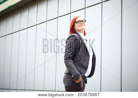 Business Concept Of Success. Serious Successful Woman Boss, In A Suit And Glasses, Rejoices At The A