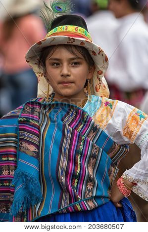 June 17 2017 Pujili Ecuador: young indigenous girl in bright color traditional clothing at Corpus Christi parade dancing in the street