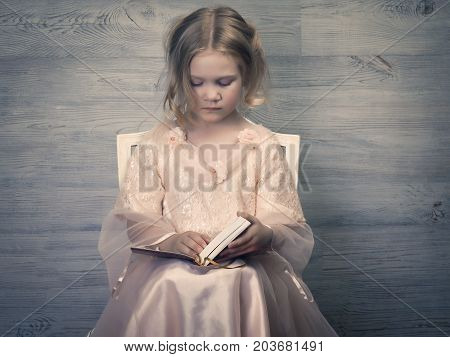 Portrait of a little girl in a ball gown with a book. Retro