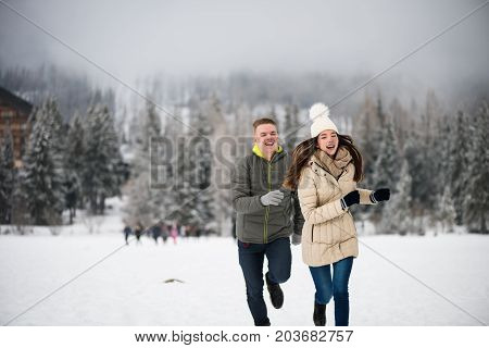 Man chasing his girlfriend in snowy mountains