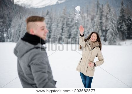 Young woman playing snowball game with her partner