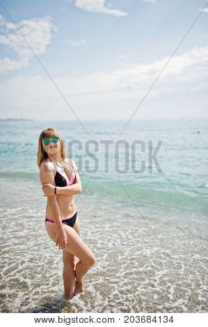 Beautiful Model Relaxing On A Beach Dressed In A Swimsuit.