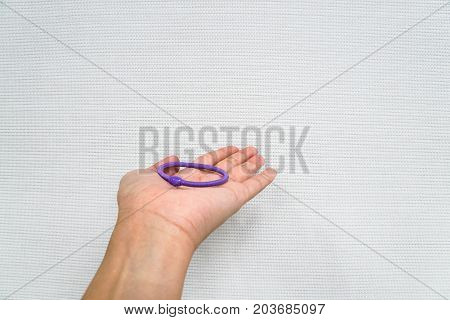 isolated woman hold purple elastic band to tie her hair