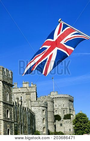 Windsor, UK, May 22, 2010 : Windsor Castle with a Union Jack flying in the foreground which is a popular visitors attraction of the historic market town