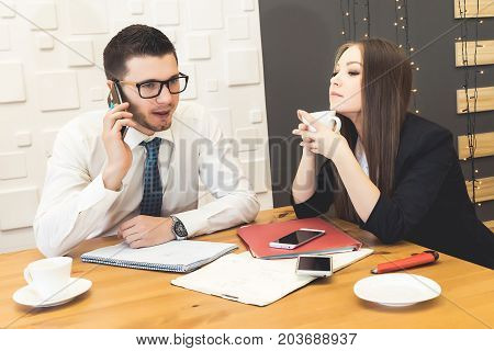 A business meeting between a man and a woman. They are sitting at the desk. A man is talking on the phone.