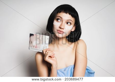 A pretty girl with black hair looks after the skin, thinks, looks away, holds a magazine