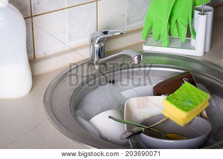 Sink full of washing dishes filled with dish soap water.