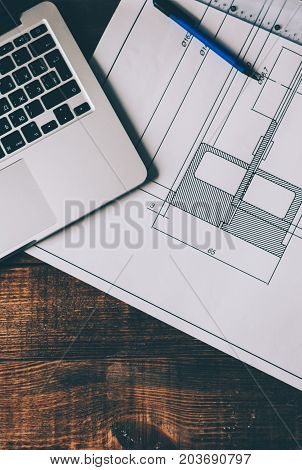 Top view of drawing with architecture sketch, laptop and pens on creative workspace