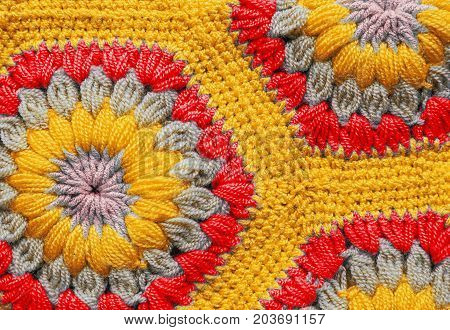 Knitted textile carpet pattern macro in yellow and red color
