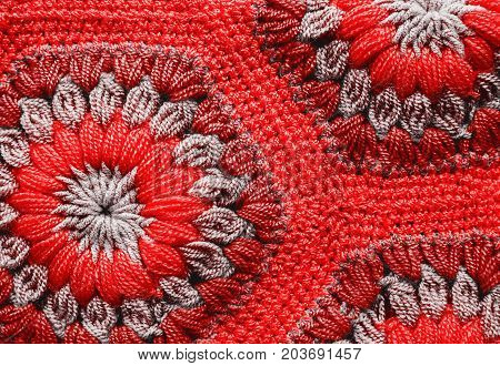 Knitted textile carpet pattern macro in red color