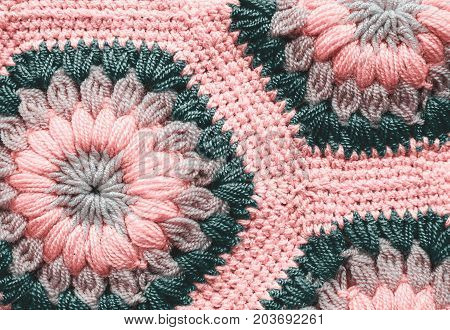 Knitted textile carpet in blue and pink color pattern macro.
