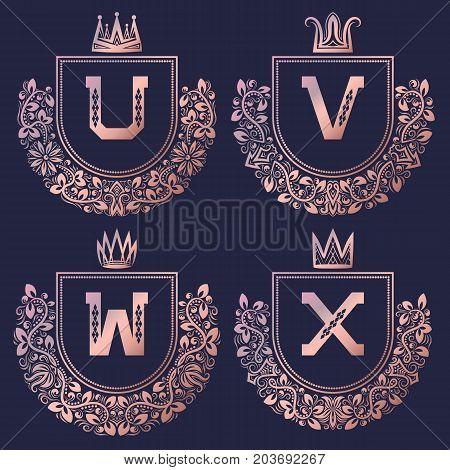 Rose gold coat of arms set in baroque style. Golden pink vintage logos with U, V, W, X monogram.