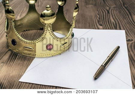 The bill. Order to rise. Order of appointment. Resolution. Document signing. Royal decree. Paper pagegolden pen and gold crown on the table.