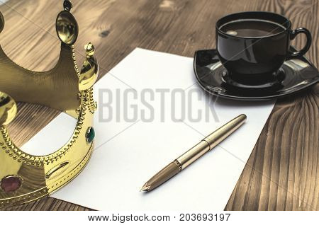 The bill. Order to rise. Order of appointment. Resolution. Document signing. Royal decree. Paper pagegolden pencup of coffee and gold crown on the table.