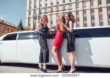 Beautiful women near a limousine drink champagne.
