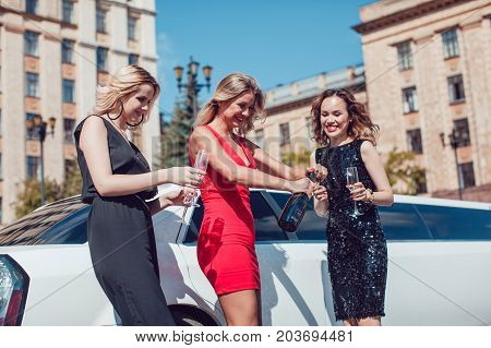 Beautiful women near the limousine have fun and drink champagne. Women open a bottle of champagne.