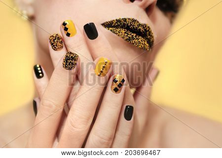 Festive yellow black manicure and makeup on a girl closeup on yellow background.Nail art.