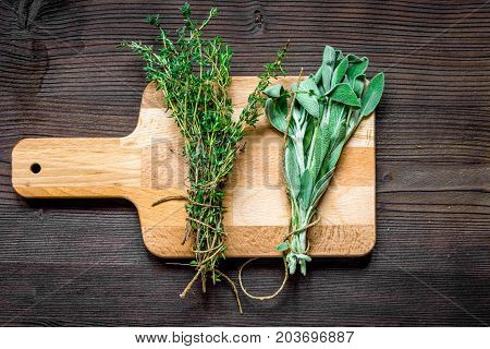bundle of sage and thyme on wooden board top view.