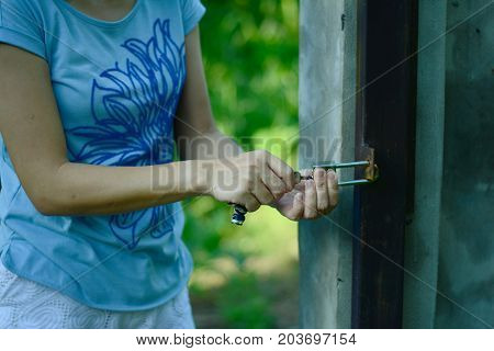 a woman holding a key and put it into a lock