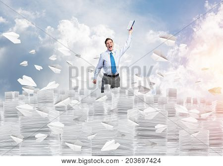 Businessman keeping hand with book up while standing among flying paper planes with cloudly skyscape on background. Mixed media.