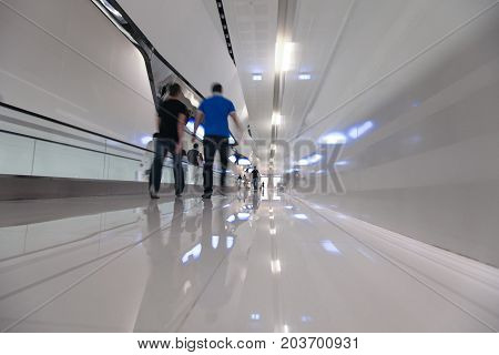 Blured people step forward on a long white corridor