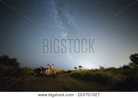 Young beautiful biker woman with motorcycle under stars of our home galaxy Miky Way. Female biker on field at night