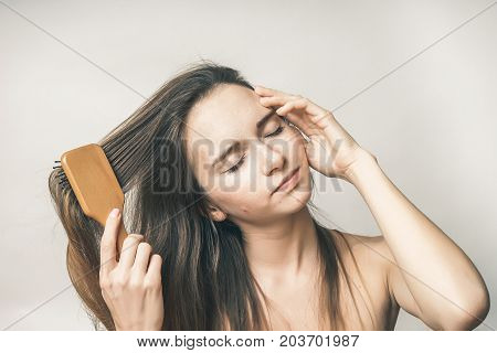 Young woman with pleasure with closed eyes combs hair comb
