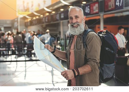 Portrait of cheerful bearded mature man watching at chart while standing in airport. Tourism concept