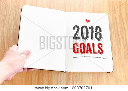 Hand Holding Open Notebook With 2018 Goals Lay It On Wooden Table,resolutions Of Life